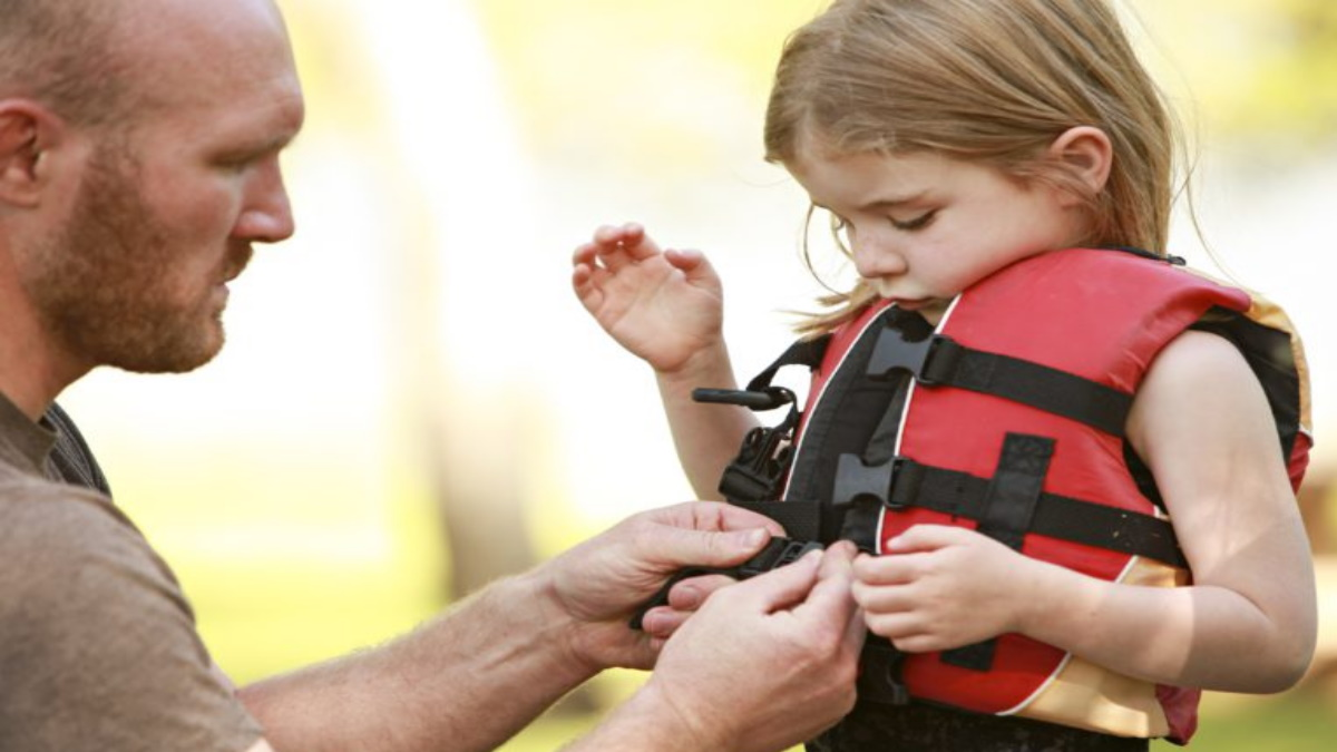 Father putting a life jacket on his daughter.