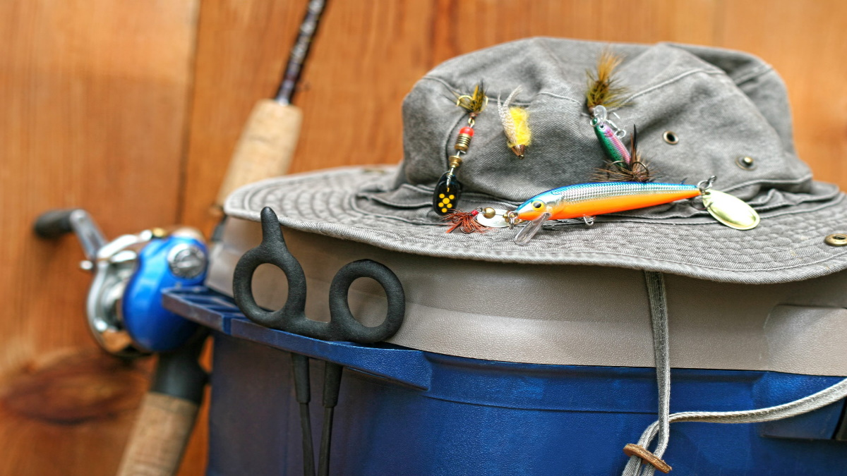Fishing hat with fishing lures on it.