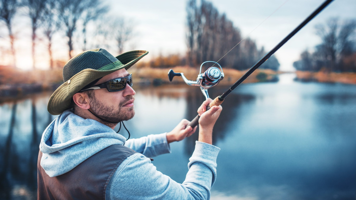Man with sunglasses casting a spinning rod.