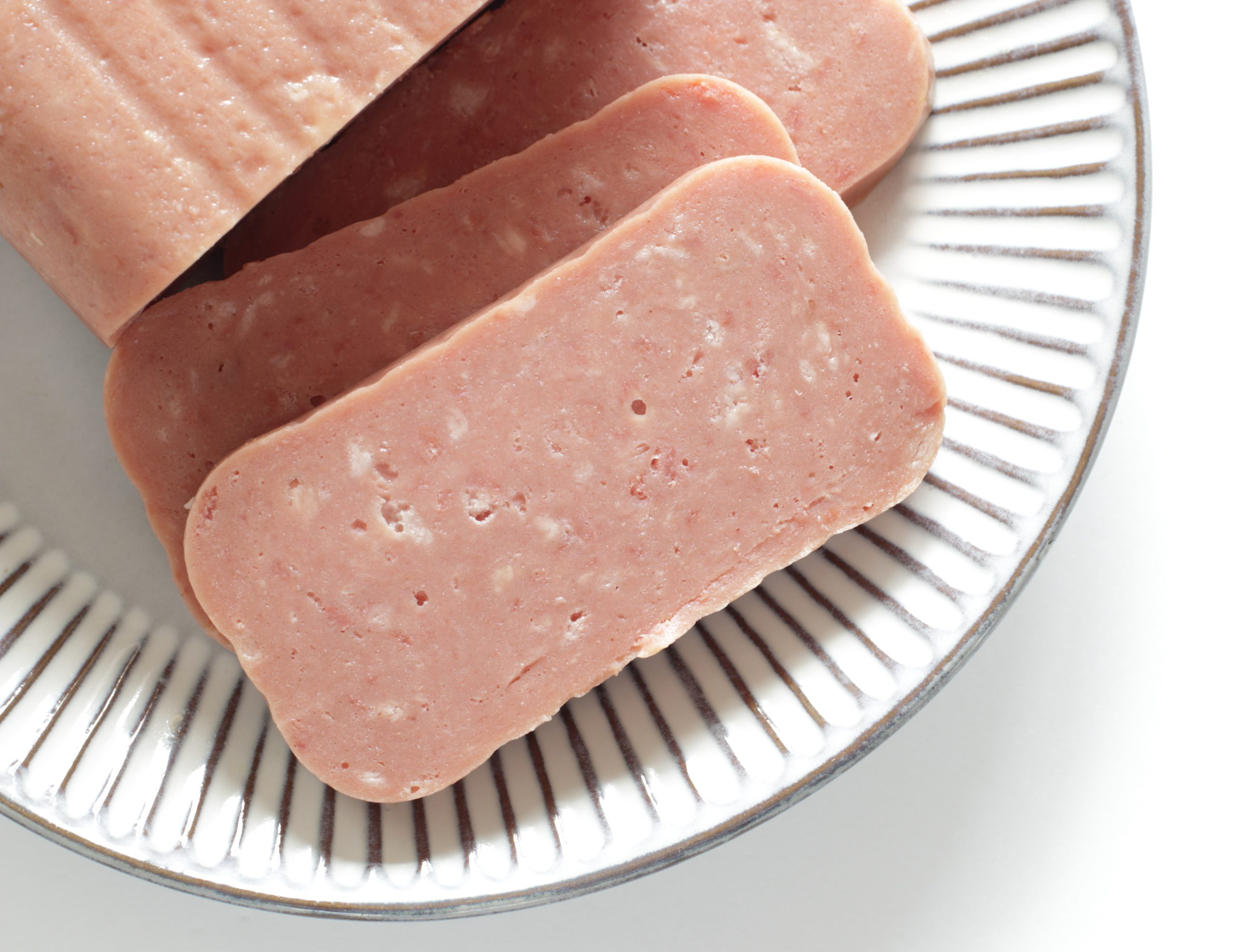 Luncheon meat sliced and resting on a plate isolated on a white background.