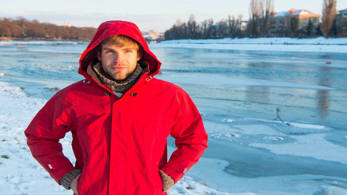 Man in a warm jacket on a frozen lake with it snowing.
