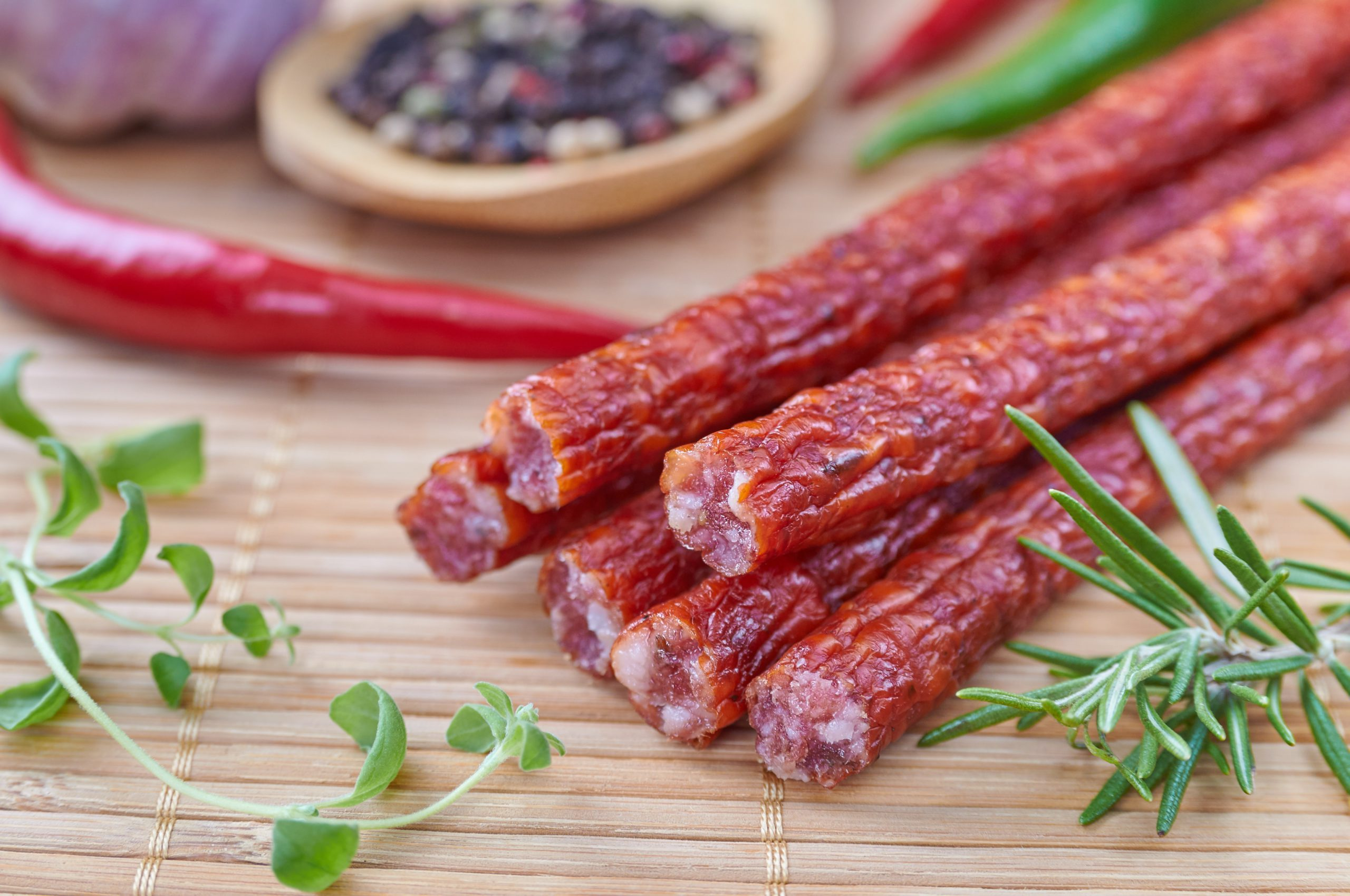 Meat sticks on a wooden table with a pepper and herbs.
