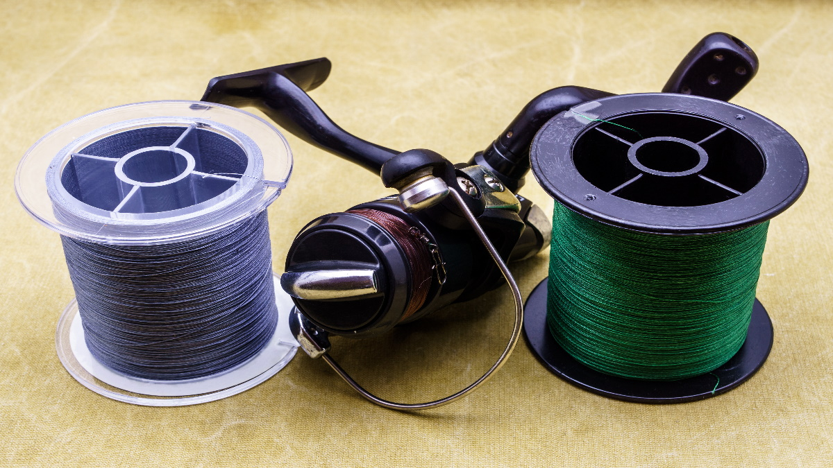 Different fishing lines on a table beside a spinning reel.