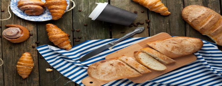 Bread slice with bread rolls, a knife, a coffee cup, and a cutting board on a picnic blanket.