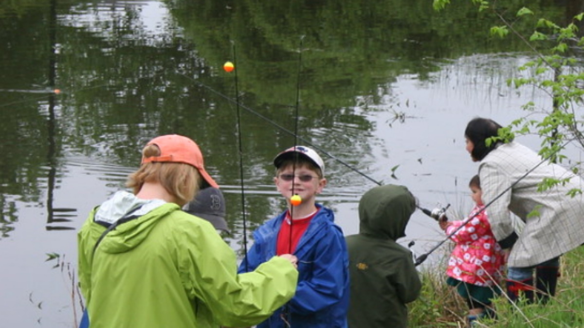 People fishing with bobbers in a small pond.