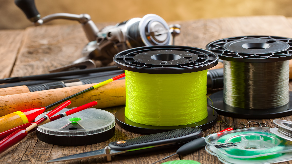Fishing line spools on a tablw with bobbers and hooks. on a table.