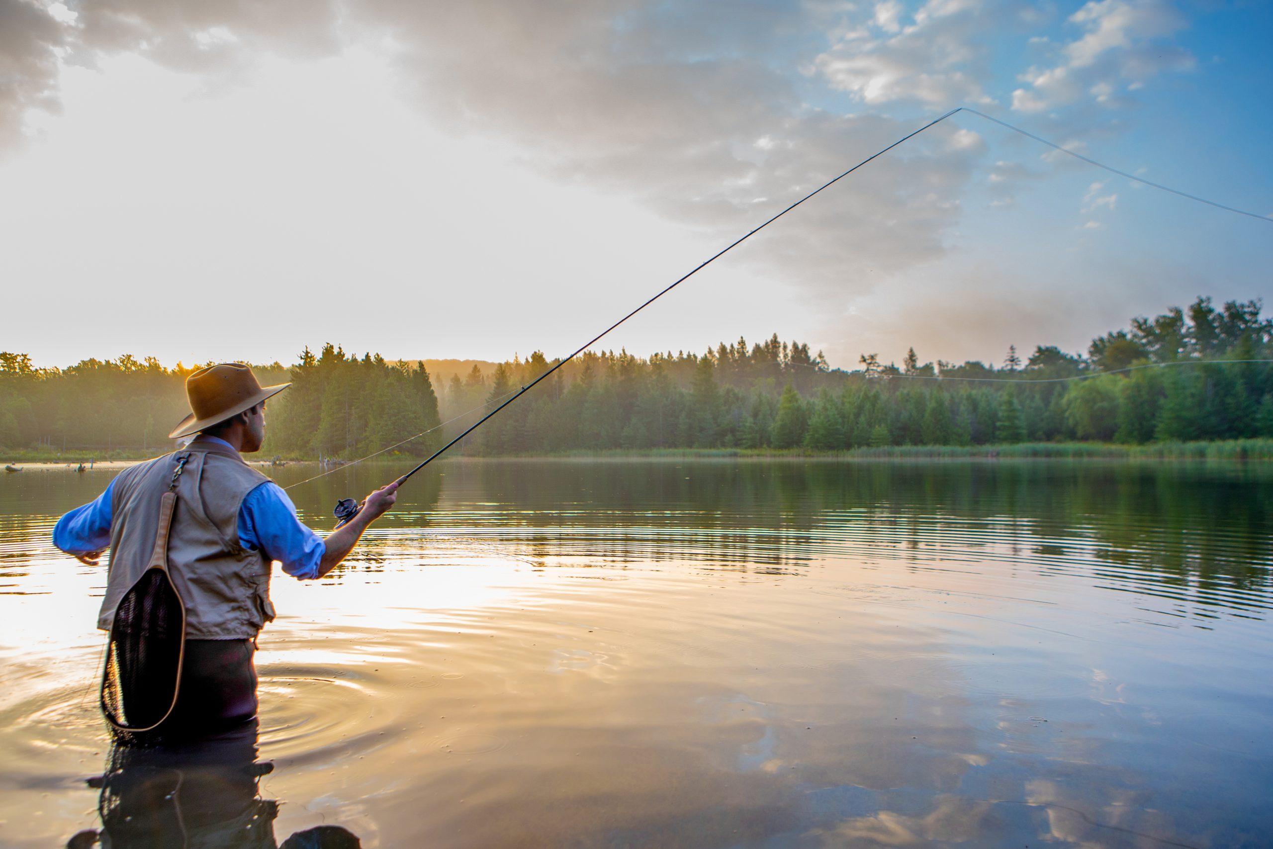Man casting a fly rod into the water at sunrise.