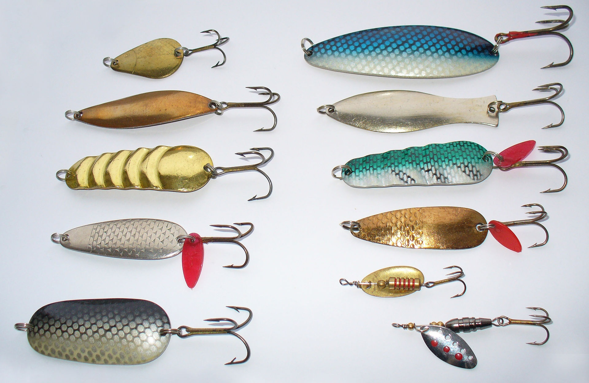 Spoon lures with hooks on a white background.