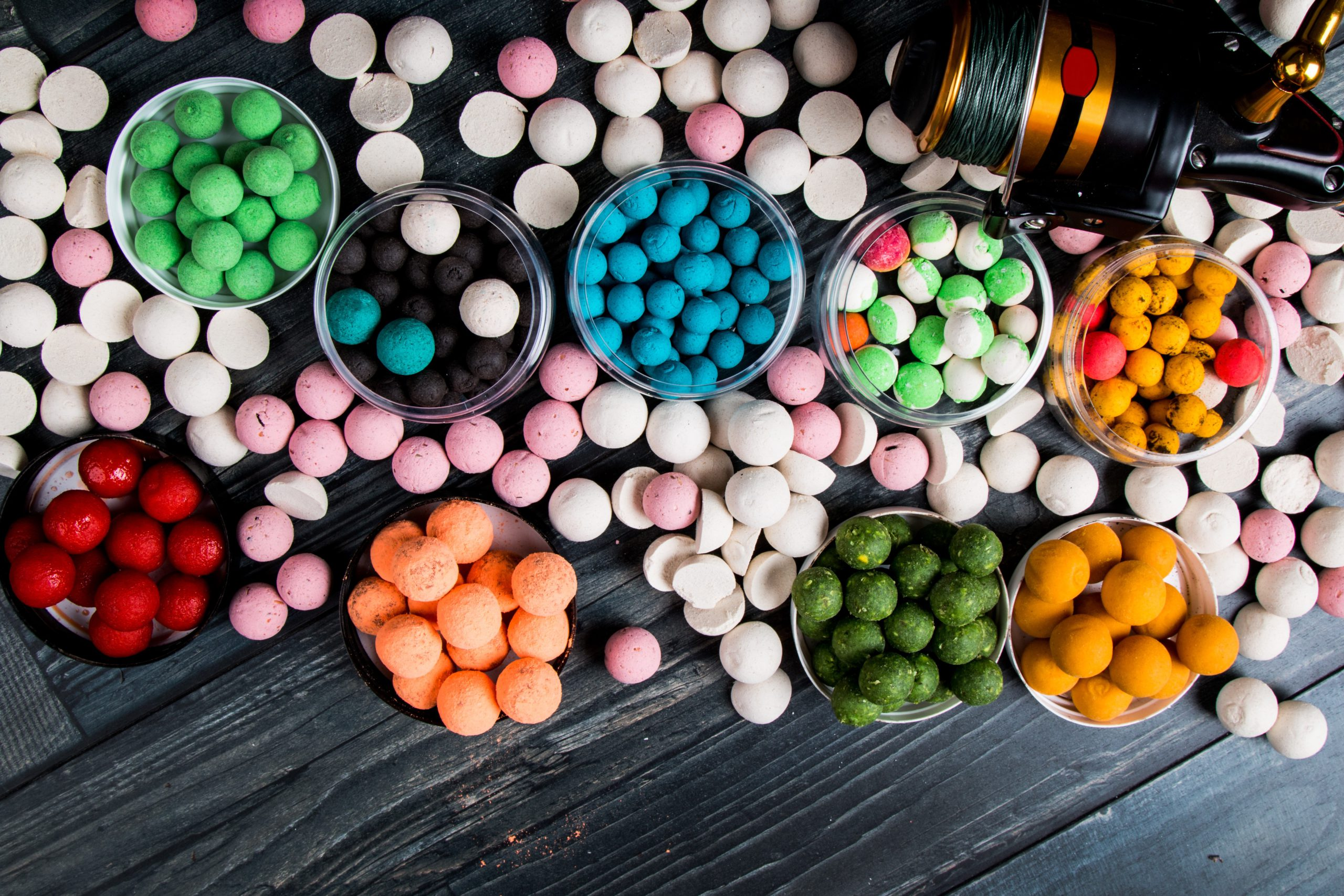 A lot of different colored carp boilies on a wooden table.