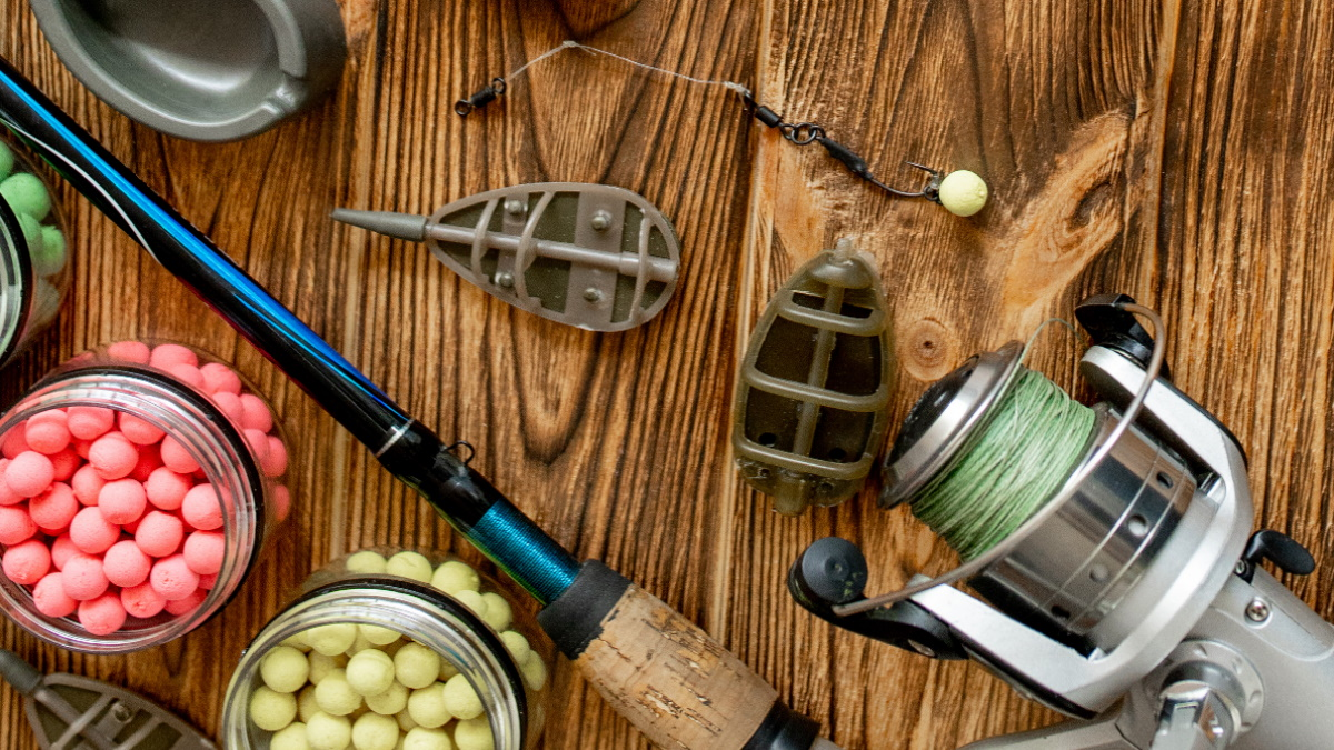 Different colored boilies and other carp fishing equipment on a wooden surface.