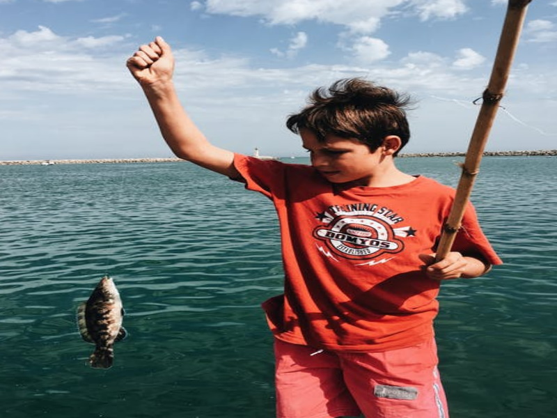 Kid holding a fish on the end of a fishing line next to water.