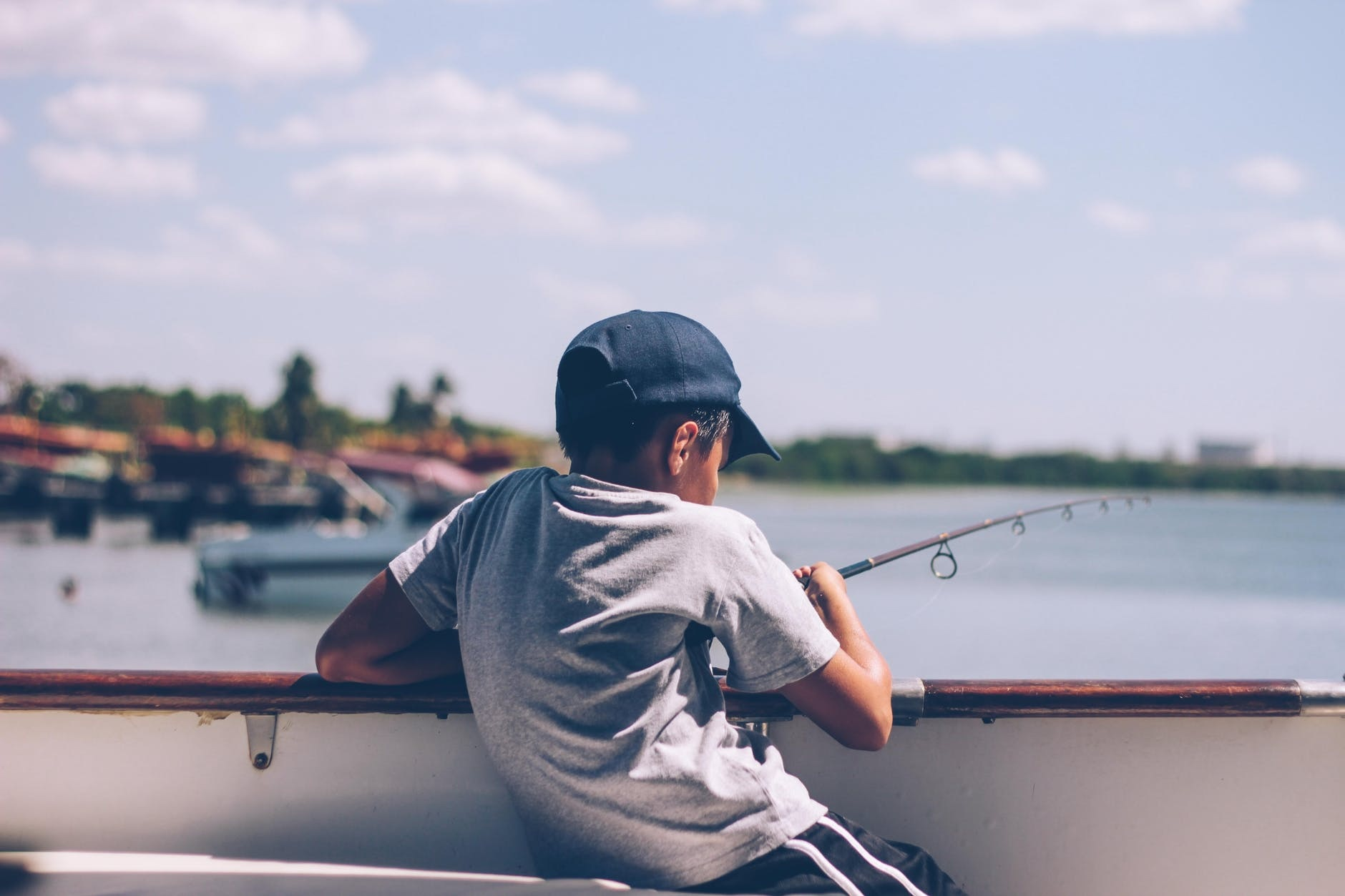 Kid with a cap and fishing rod on a pier with line sitting in water.