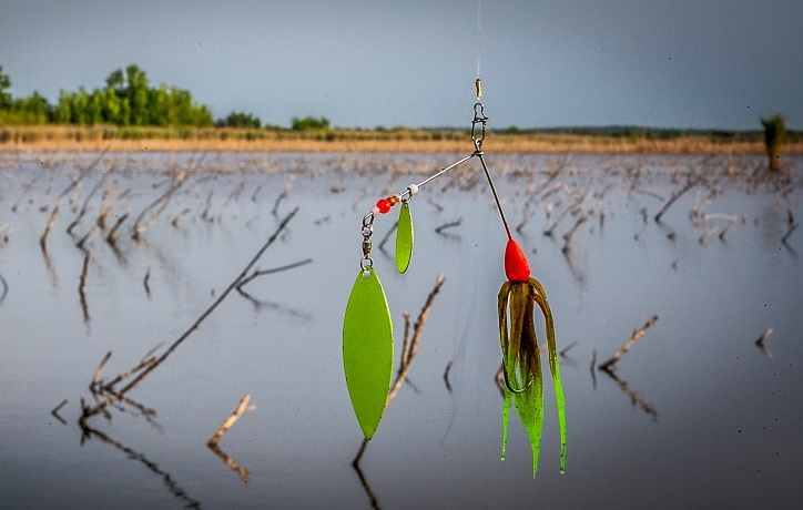 Safety pin spinner lure hanging above a bass pond.