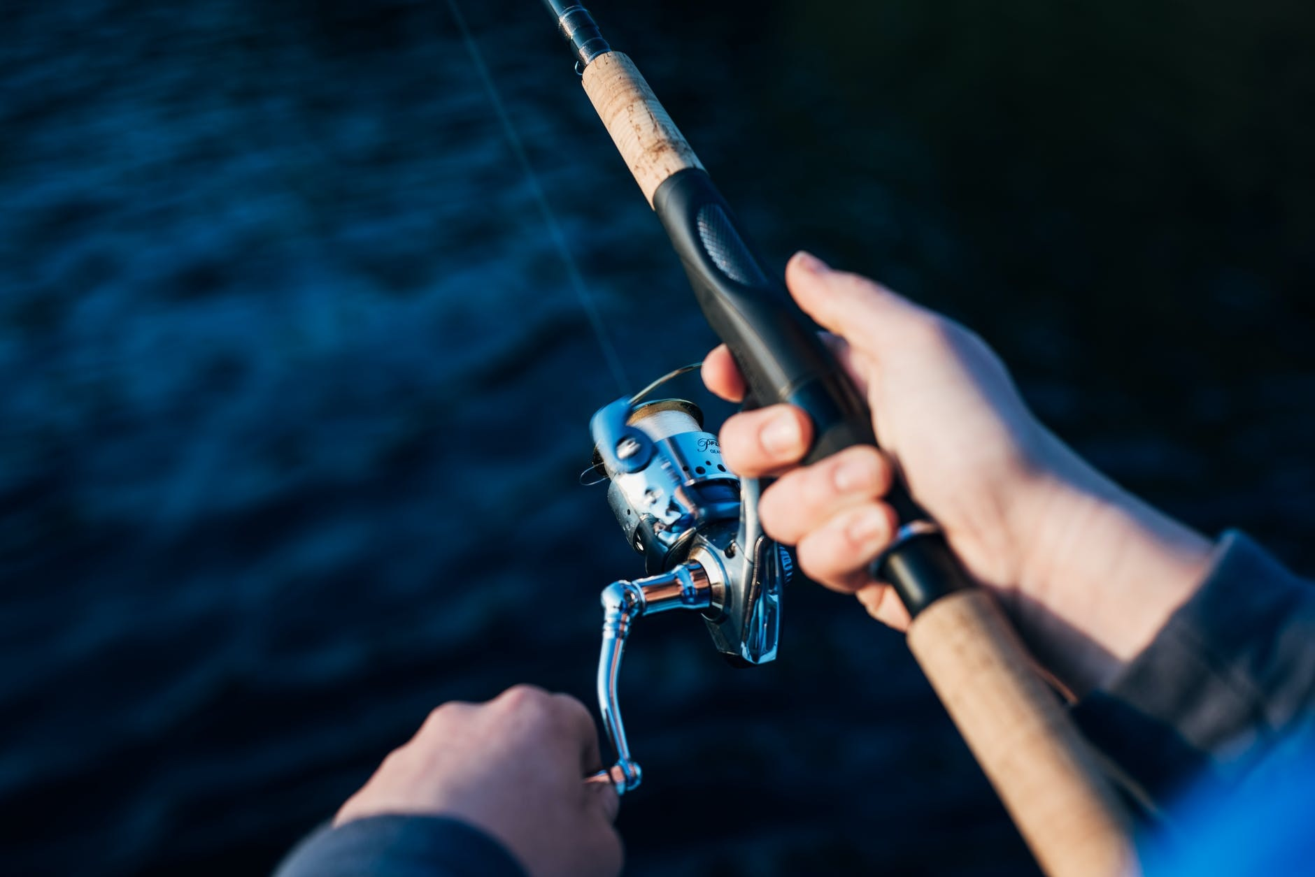 Hands holding a spinning rod and reel above blue water.
