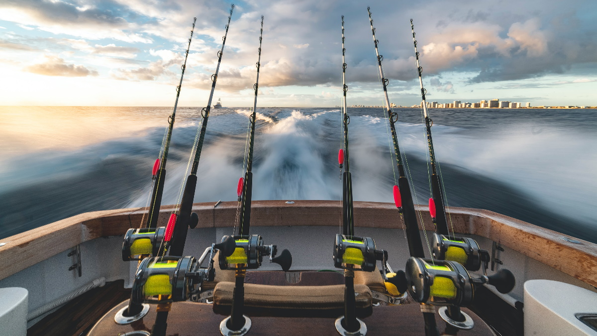 Big black baitcasting fishing rods with bobbers on the back of a wooden boat in the water.