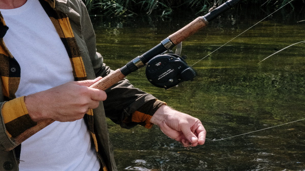 Man with a big baitcasting rod holding the line between two fingers in a stream.